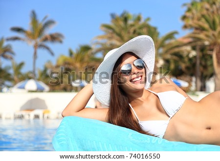 Woman sunbathing in bikini at tropical travel resort. Beautiful young Asian Caucasian woman smiling lying on sun lounger near pool. - stock photo