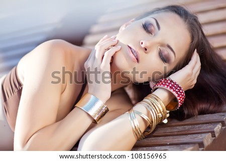 Woman sunbathing in bikini at tropical travel resort. Beautiful young woman lying on sun lounger.