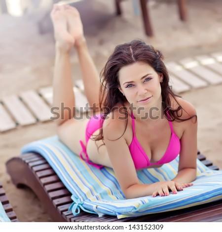 Woman sunbathing in bikini at tropical travel resort. Beautiful young woman lying on sun lounger. - stock photo