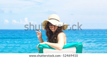 Woman sunbathing on plastic chair at the beautiful beach - stock photo