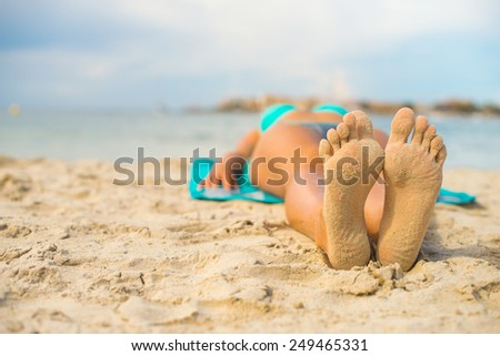 Woman sunbathing on sand. Place for text. - stock photo