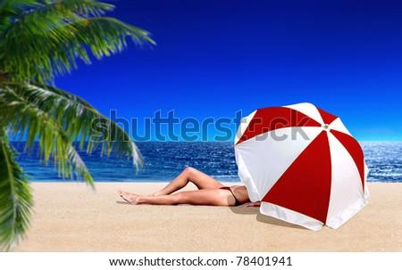 Woman sunbathing on the beach - stock photo