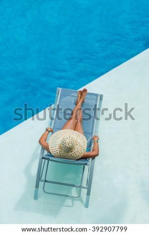 woman suntanning enjoying on sunbed at swimming pool - stock photo