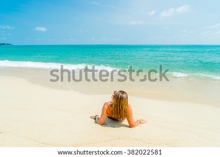 Woman suntanning on the beach on the beach - stock photo