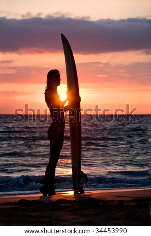 woman surfer with surfboard on tropical beach at sunset