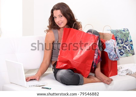 Woman surrounded by bags shopping on-line
