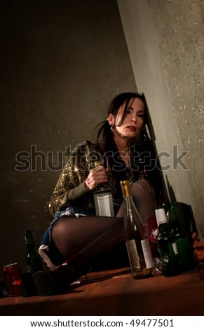 Woman surrounded by booze bottles in a hallway - stock photo