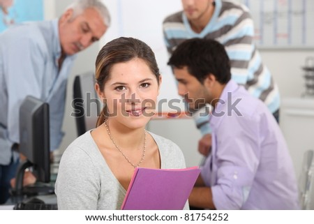 Woman surrounded by her colleagues at work - stock photo