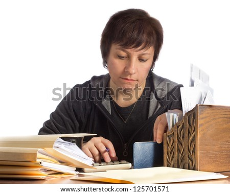 Woman surrounded by papers works on household finances and income tax - stock photo