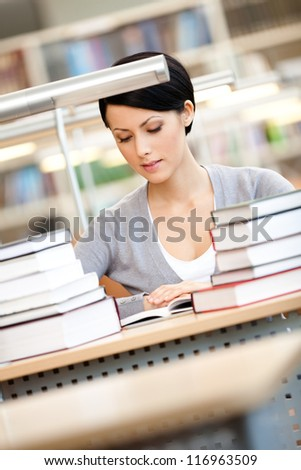 Woman surrounded with piles of books reads sitting at the desk at the library. Knowledge concept - stock photo