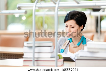 Woman surrounded with piles of books reads sitting at the desk at the library. Studying process