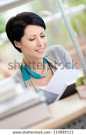 Woman surrounded with piles of books reads sitting at the desk at the reading hall. Training process - stock photo