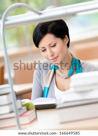 Woman surrounded with piles of books reads sitting at the table at the library