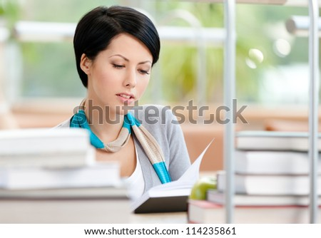 Woman surrounded with piles of books reads sitting at the table at the library. Academic achievement