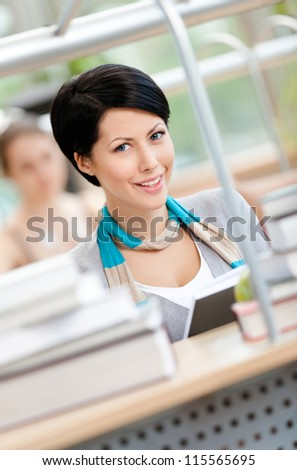Woman surrounded with piles of books reads sitting at the table at the library. Studying process
