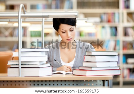 Woman surrounded with piles of books reads sitting at the table at the reading hall - stock photo