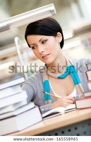 Woman surrounded with piles of books reads sitting at the table at the reading hall. Academic achievement