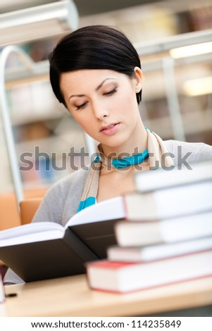 Woman surrounded with piles of books reads sitting at the table at the reading hall. Knowledge concept