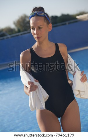 woman swimmer holding towel by swimming pool - stock photo