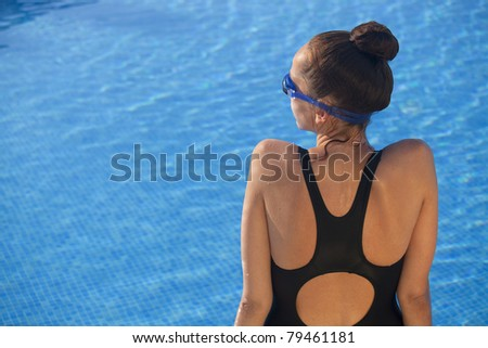 woman swimmer sitting by the swimming pool - stock photo