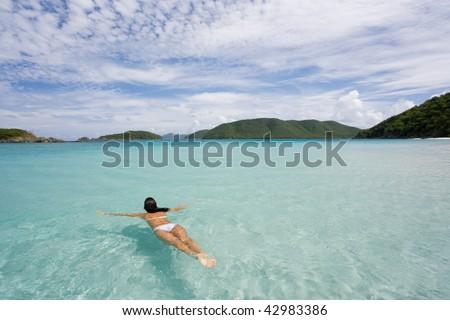 woman swimming at tropical island beach in white bikini on vacation - stock photo