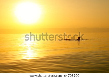 Woman swimming in a salt water of Dead sea. - stock photo