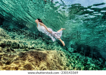 Woman swimming near rock in transparent blue sea, wearing white dress, relaxation in refreshing water, summer enjoyment concept - stock photo