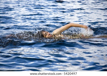 woman swimming the crawl through the blue forest lake