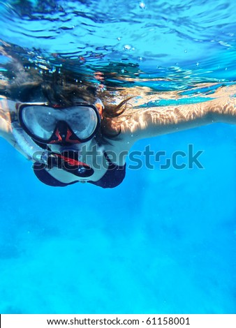 Woman swimming under water in snorkeling mask for looking marine life - stock photo