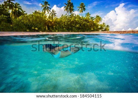 Woman swimming underwater, enjoying transparent sea and tropical nature of island, active lifestyle, summertime adventure, spending vacation in blue lagoon - stock photo