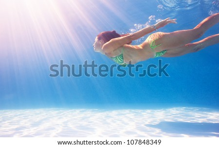 Woman swimming underwater in a blue pool. - stock photo
