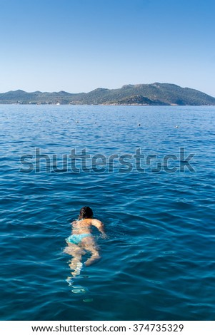 Woman swims towards an Island off the coast of Turkey