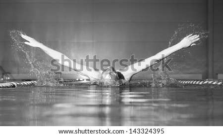 woman swims using the butterfly stroke in indoor pool - stock photo