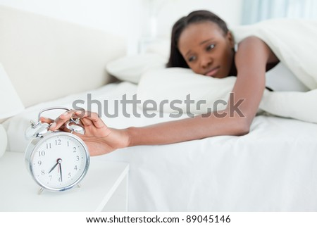 Woman switching off her alarm clock in her bedroom - stock photo