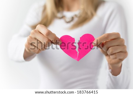 Woman symbolically tearing up pink paper heart - stock photo