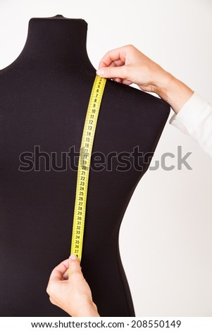 Woman tailor making measurements on the mannequin - stock photo