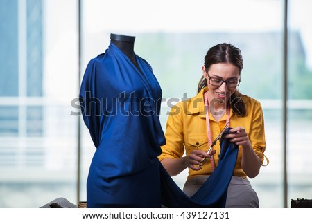 Woman tailor working on new clothing - stock photo