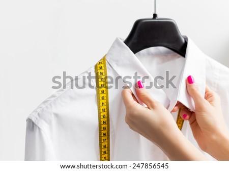 Woman tailoring business shirt - stock photo