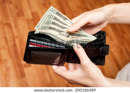 Woman take dollar money out from wallet - stock photo