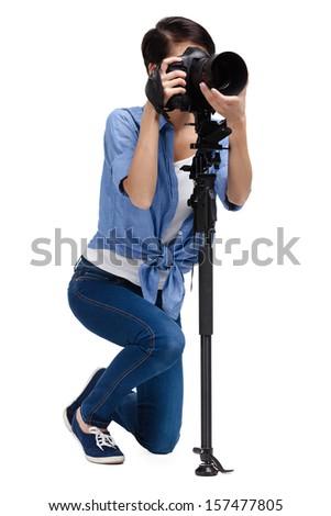 Woman takes images holding photographic camera, isolated on white background - stock photo