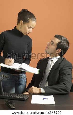 Woman takes notes for a business man sitting at a desk. Vertically framed photo.