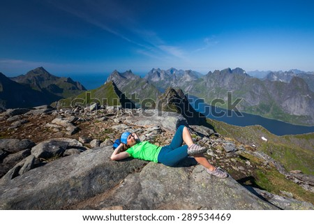 Woman takes rest on top of mountain in Norway - stock photo