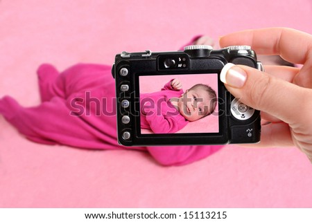 woman takes snapshot of a small one week old newborn baby girl on a pink background - stock photo