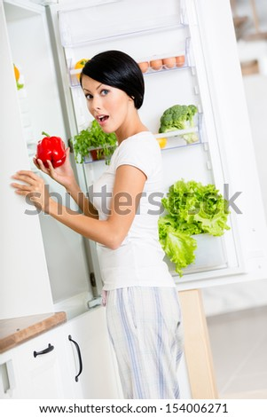 Woman takes sweet pepper from the opened fridge full of vegetables and fruit. Concept of healthy and dieting food