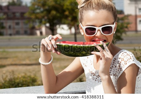 Woman takes watermelon from the opened fridge full of vegetables and fruit. Concept of healthy and dieting food - stock photo