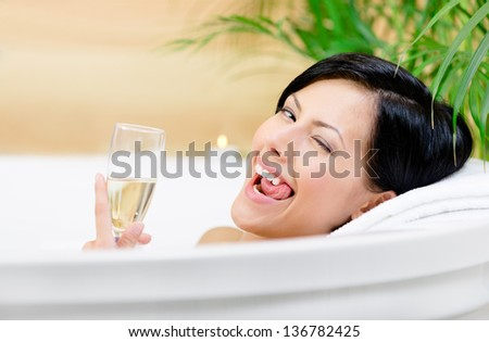 Woman taking a bath with suds drinks champagne, winks and relaxes - stock photo