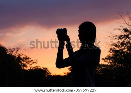 woman taking a photo and sunset