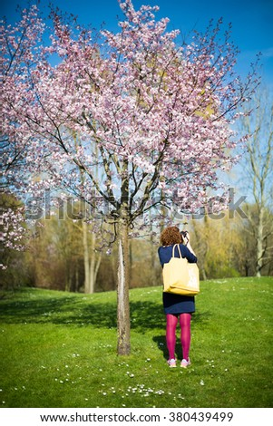 woman taking a photo of a blooming cherry tree