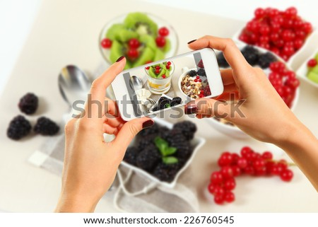 Woman taking a photo of breakfast with smartphone - stock photo