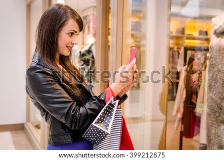 Woman taking a photo of window display in mall - stock photo